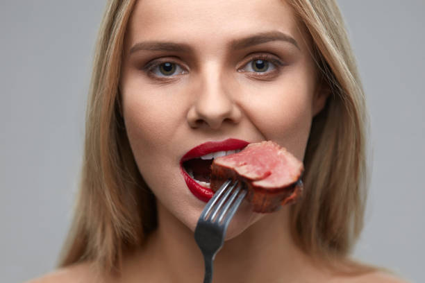 Woman Eating Meat. Closeup Of Beautiful Female Face Biting Meat Woman Eating Meat. Closeup of Healthy Hungry Girl With Beautiful Face, Red Lips Eats Delicious Grilled Meat. Female Mouth Biting Piece Of Tasty Beef Steak On Fork. Nutrition Concept. High Resolution red meat stock pictures, royalty-free photos & images