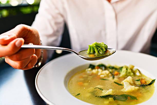 minestrone donna mangiare zuppa di verdure - minestrone foto e immagini stock