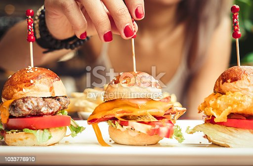 Woman eating mini burgers with fast food with French fries chips