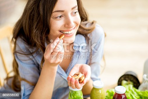 istock Woman eating nuts 669558530