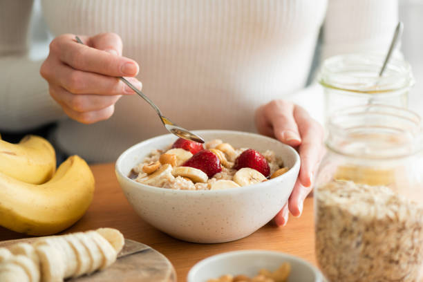 Woman eating oatmeal porridge Woman eating oatmeal porridge with banana, strawberries and nuts. Healthy breakfast at the sunny morning kitchen table breakfast stock pictures, royalty-free photos & images