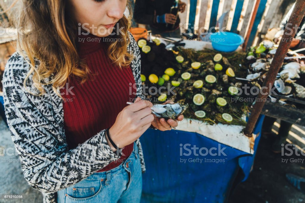 Woman eating oyster  in the Port of Essaouira stock photo