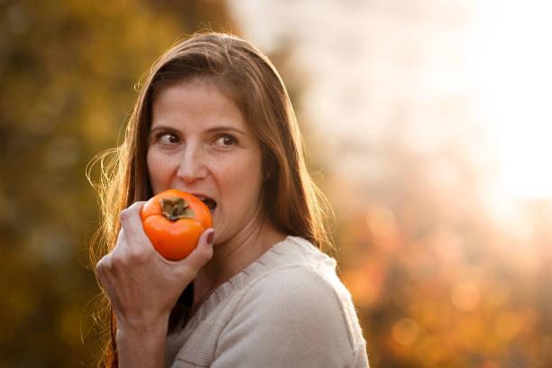 frau essen kaki - sharonfrucht stock-fotos und bilder