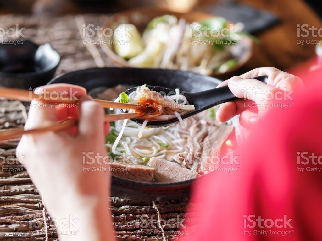 woman eating pho with sriracha using chopsticks and spoon together photo libre de droits