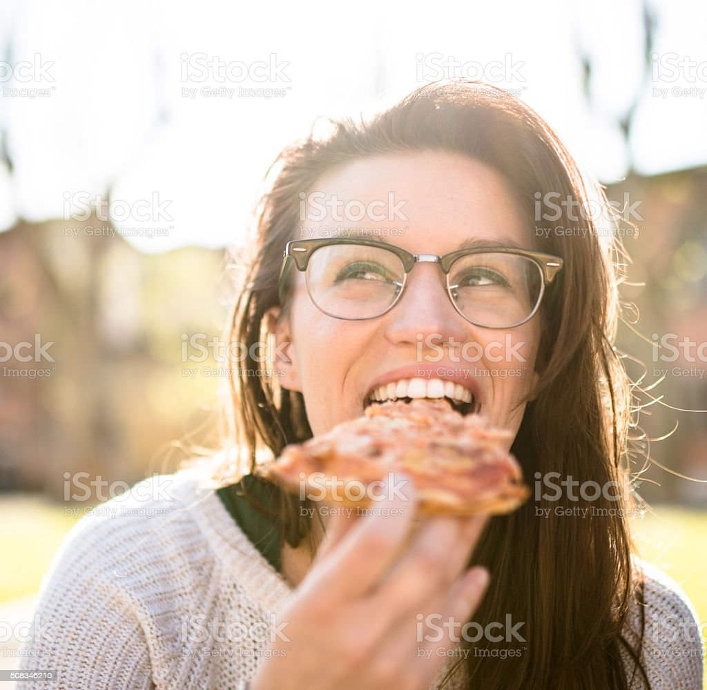 woman eating pizza at dusk on the city stock photo