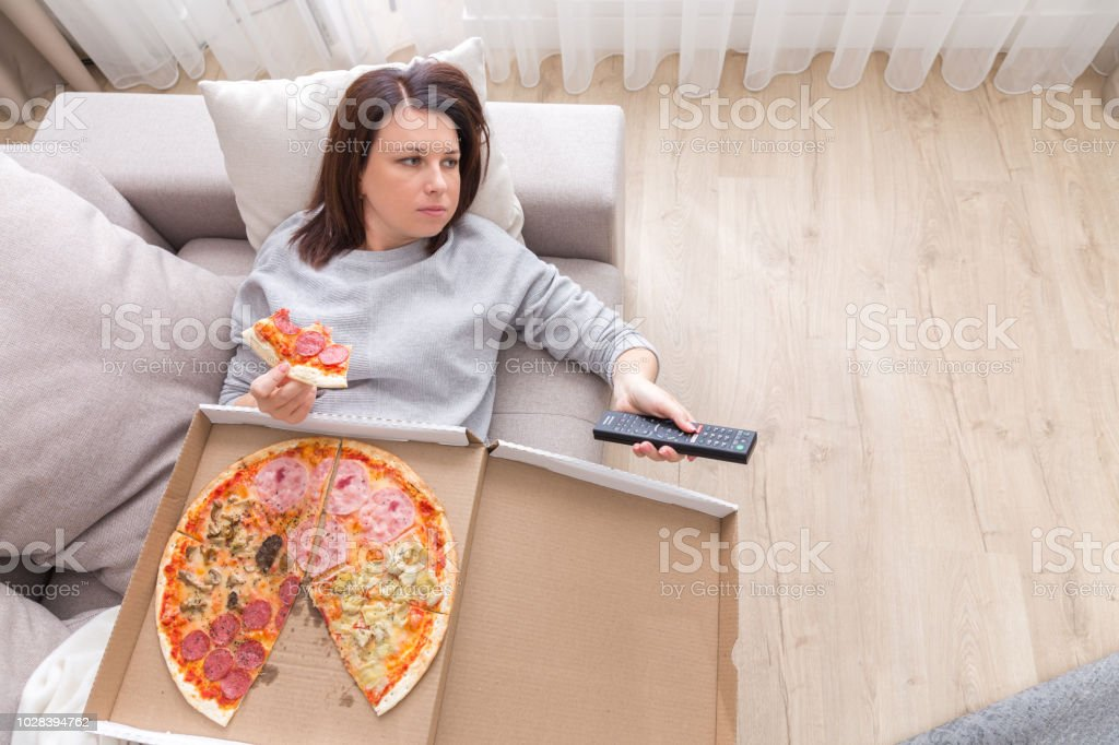 woman eating pizza image taken from above Woman laying on couch with cell phone eating pizza Above Stock Photo