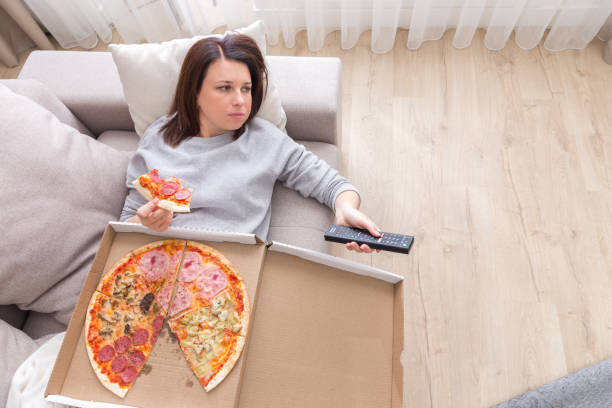 woman eating pizza image taken from above stock photo