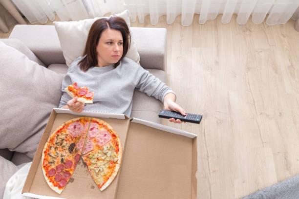 vrouw eten pizza beeld genomen van bovenaf - lazy stockfoto's en -beelden