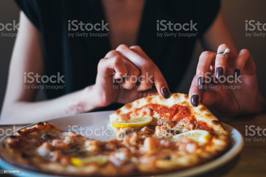 Woman eating pizza stock photo