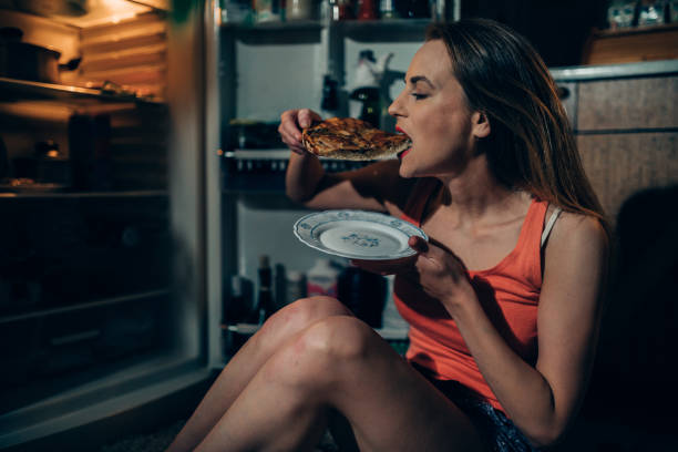 Woman eating pizza slice in front of the refrigerator late night stock photo
