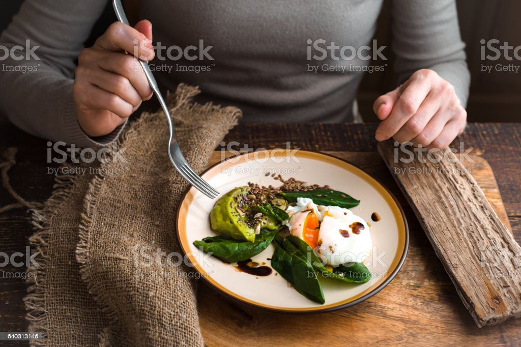 Woman eating poached egg with avocado cream horizontal - Royalty-free Adult Stock Photo