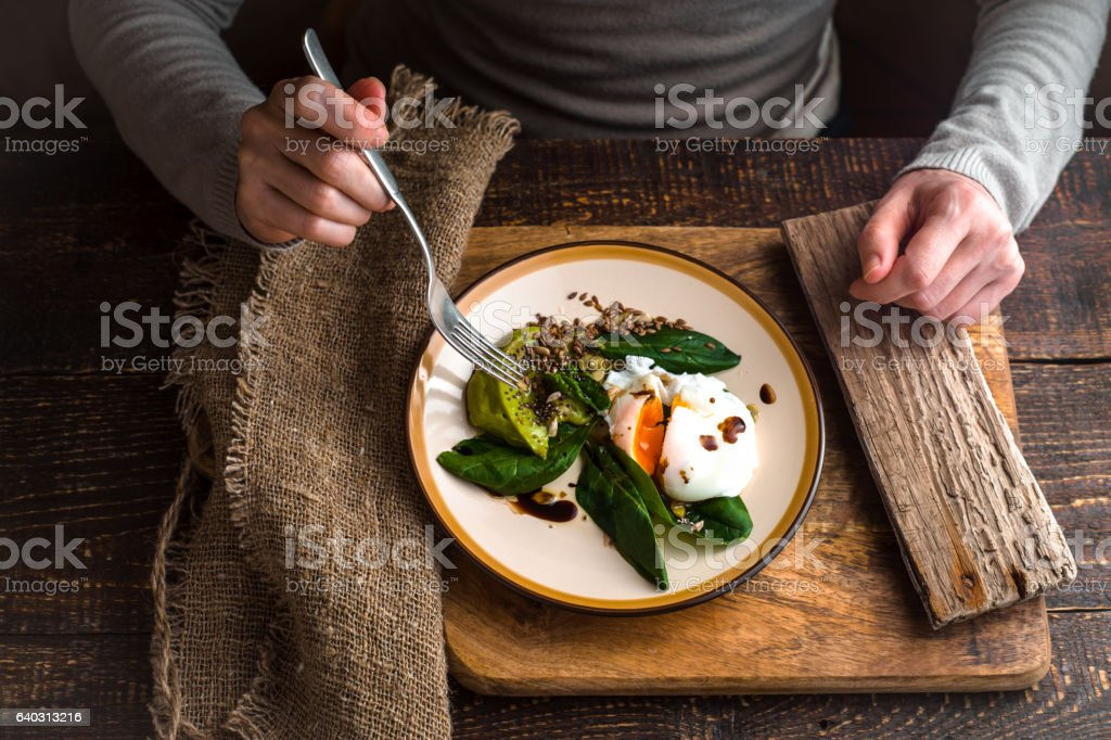 Woman eating poached egg with avocado cream top view – Foto