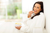istock woman eating popcorn on bed 479053115