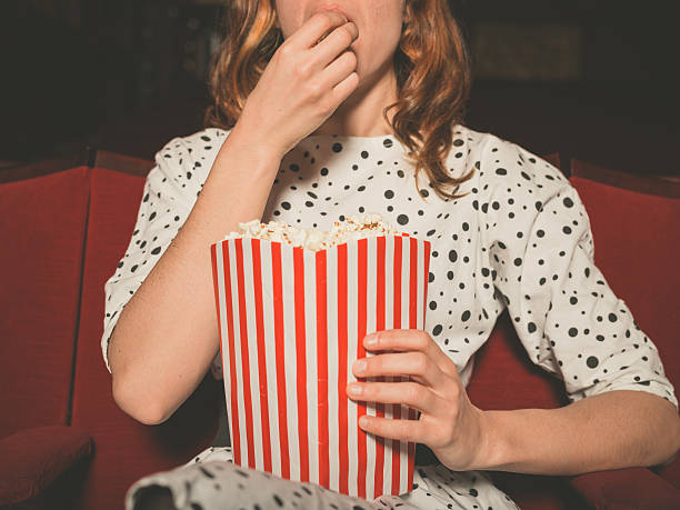 Woman eating popcorn while watching a movie stock photo