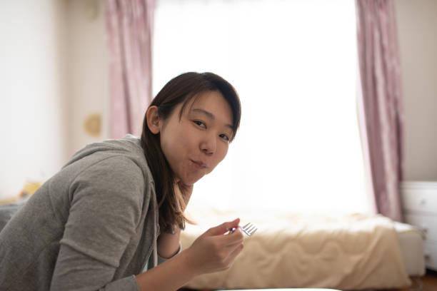 部屋でサラダを食べる女性 - 独身の若者 ストックフォトと画像