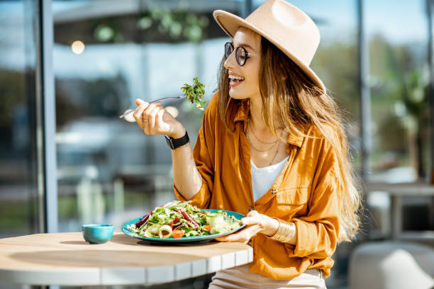 Woman eating salad on a cafe terrace stock photo