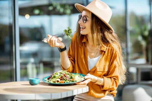 Vrouw die salade eet op een terrasje foto