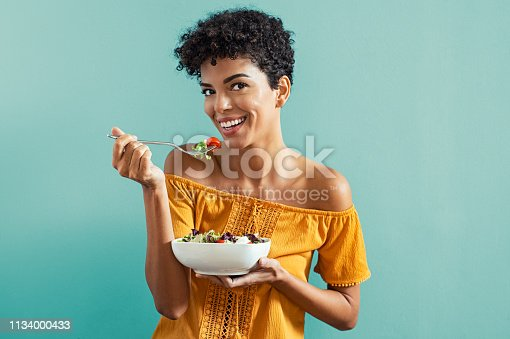 Beautiful young african woman eating fresh salad with cherry tomatoes. Portrait of happy smiling woman in diet isolated on blue background. Cheerful brazilian girl with curly hair eating fresh vegetable while looking at camera with copy space.