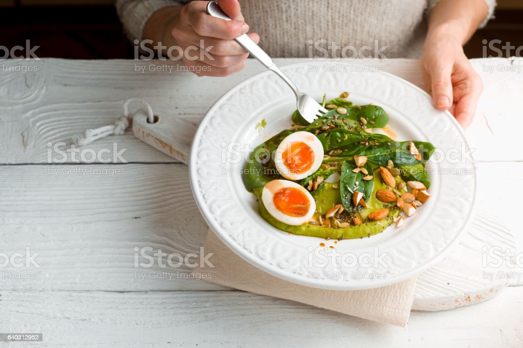 Woman eating salad with spinach, almond and eggs  horizontal – Foto