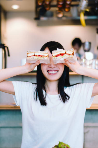 Woman Eating Sandwiches Woman Eating Sandwiches female sandwich stock pictures, royalty-free photos & images