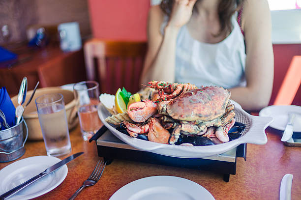 Woman eating seafood platter stock photo