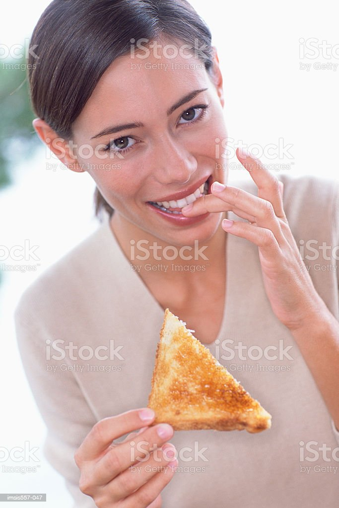Woman eating slice of toast royalty-free stock photo