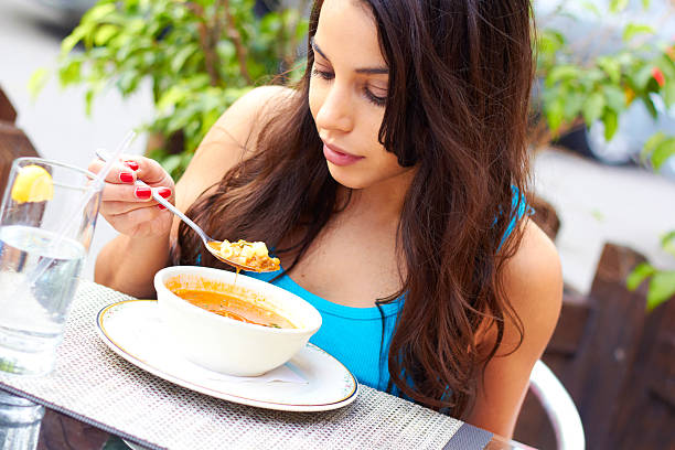 Woman Eating Soup stock photo