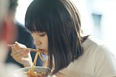 Woman eating spaghetti with chopsticks at Japanese pub in Japan