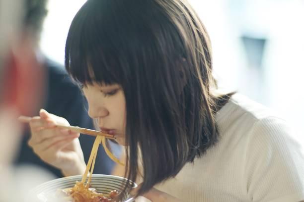 Woman eating spaghetti with chopsticks at Japanese pub stock photo
