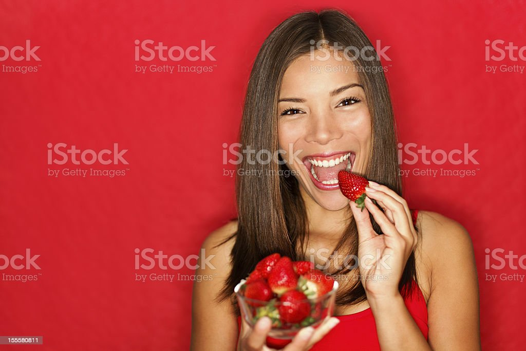 Woman eating strawberries stock photo