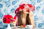 イチゴの身に着けている夏帽子を食べる女