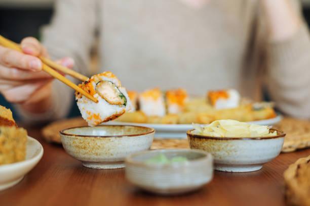 Frau isst Sushi-Brötchen – Foto