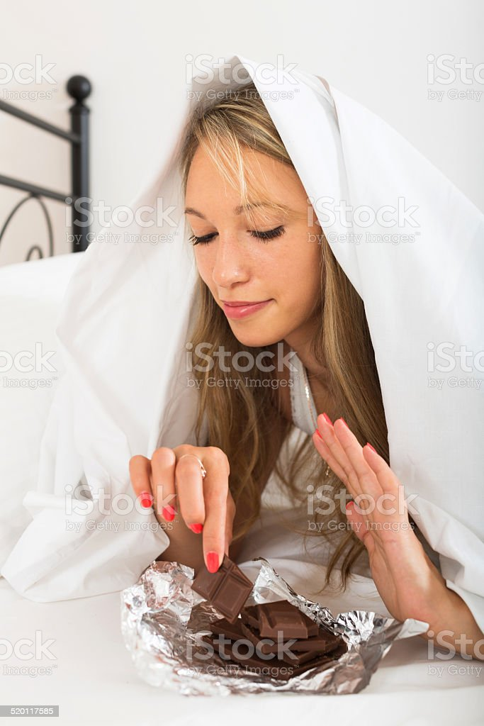 Woman eating sweet chocolate in her bedroom stock photo