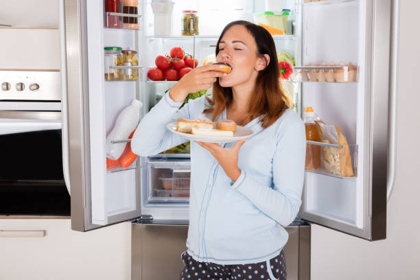 Woman Eating Sweet Food Near Refrigerator Young Woman Enjoy Eating Donut From Plate Near Refrigerator In Kitchen hungry stock pictures, royalty-free photos & images