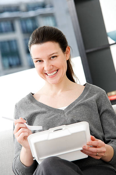 Woman Eating Take Out Food at Home or Office stock photo