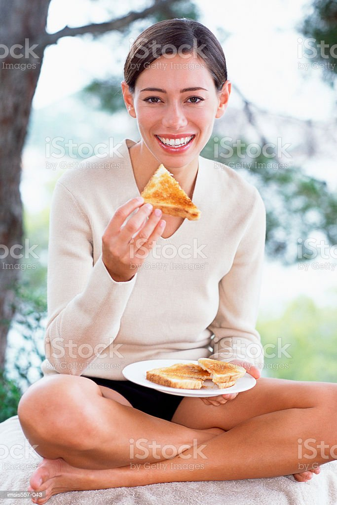 Woman eating toast in garden royalty free stockfoto