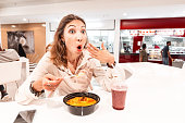 A woman eating too hot and peppery soup in an Asian fast food restaurant. Concept of spices in Oriental cuisine