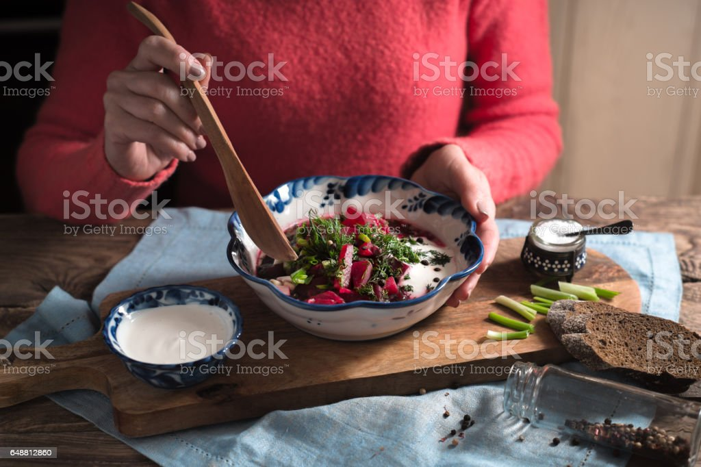 Woman eating traditional beetroot soup borsch horizontal stock photo