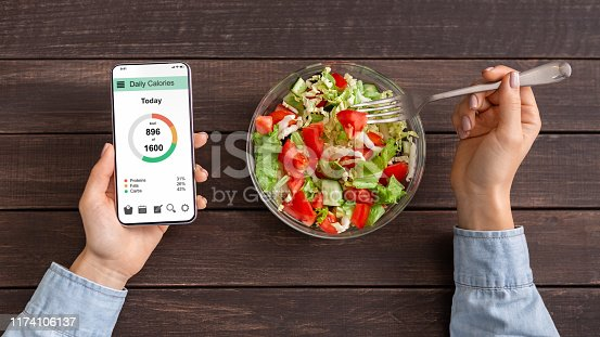 Smart eating and diet planning concept. Woman eating fresh vegetable salad and counting calories on mobile application, top view
