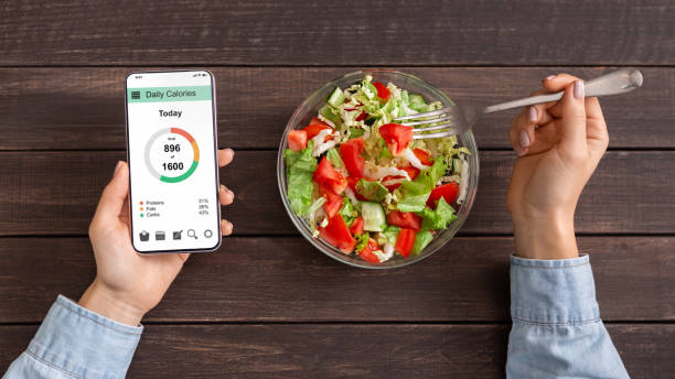 Woman eating vegetable salad and counting calories on mobile application Smart eating and diet planning concept. Woman eating fresh vegetable salad and counting calories on mobile application, top view dieting stock pictures, royalty-free photos & images