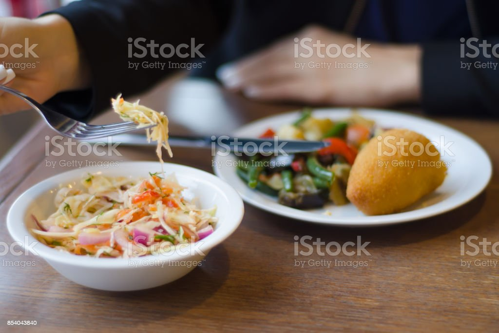 Woman eating vegetables with chicken cutlet and salad stock photo