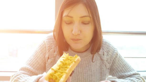 Frau isst einen Hot Dog in einem Fast-Food-Café mit Appetit – Foto