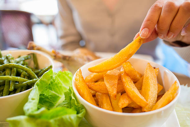 Woman eats French Fries at restaurant, salad, vegetable stock photo