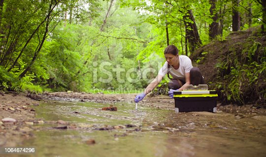Woman scientist environmentalist sitting near the creek. She taking sample of water