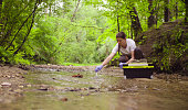 Woman scientist environmentalist sitting near the creek. She taking sample of water