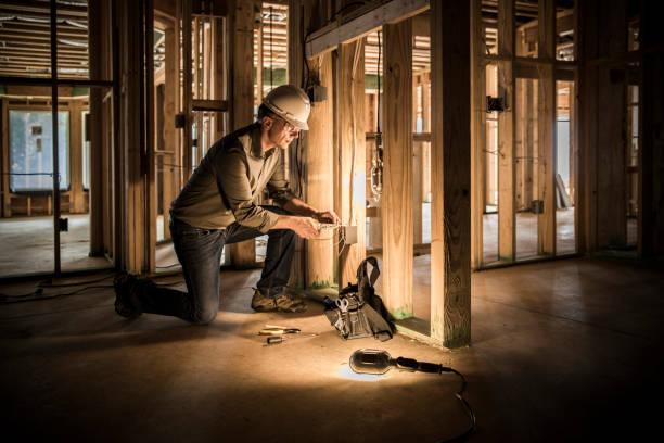 electricista de la mujer en el sitio de construcción de viviendas. - electricista fotografías e imágenes de stock