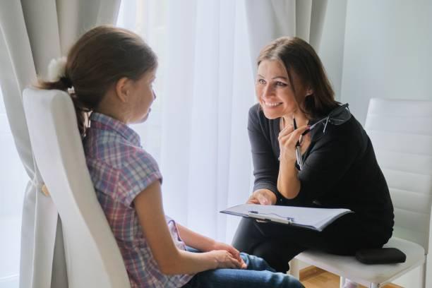 Mujer maestra de escuela primaria probando hablar con la niña - foto de stock
