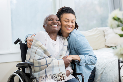 504241549 istock photo Woman embraces her wheelchair-bound mother 932074776