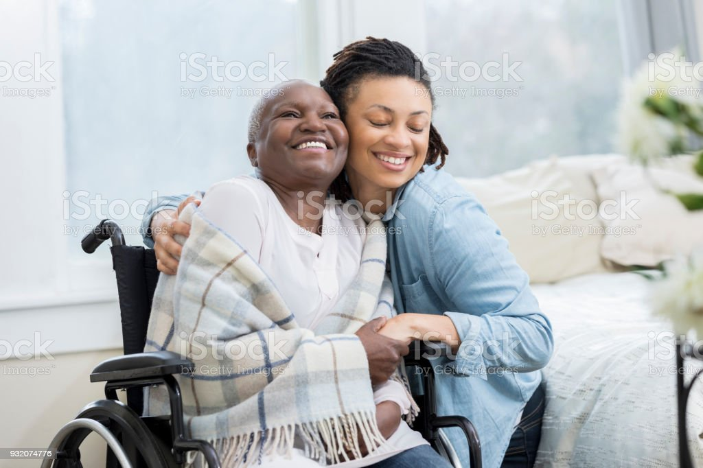 Woman embraces her wheelchair-bound mother stock photo