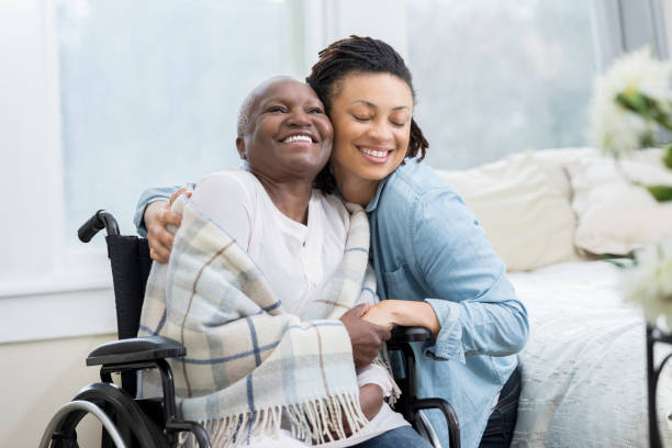 woman embraces her wheelchair-bound mother - personale sanitario foto e immagini stock